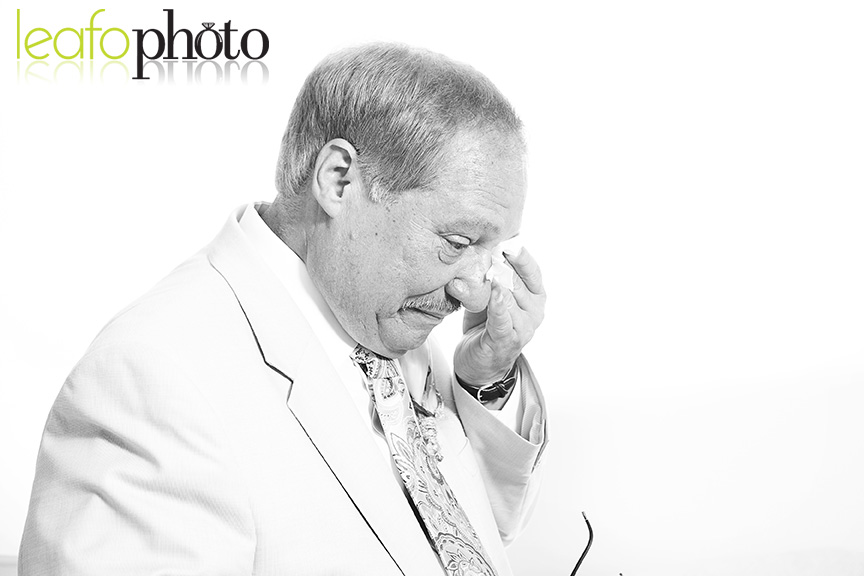 Candid moment where father sees daughter on her wedding day and wipes tears from his eyes