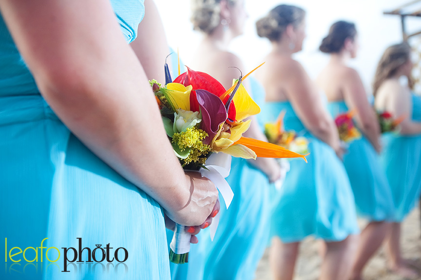 Bridesmaids holding bouquets on beach